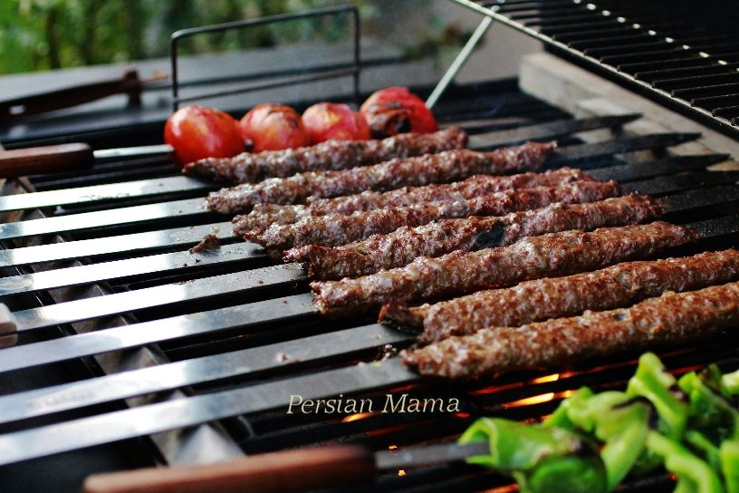 Grilling Kabob Koobideh with tomatoes and peppers on metal skewers