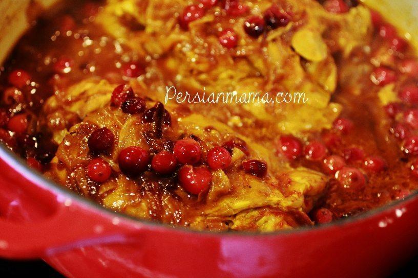 tender turkey in saffron broth with fresh cranberries in Dutch oven
