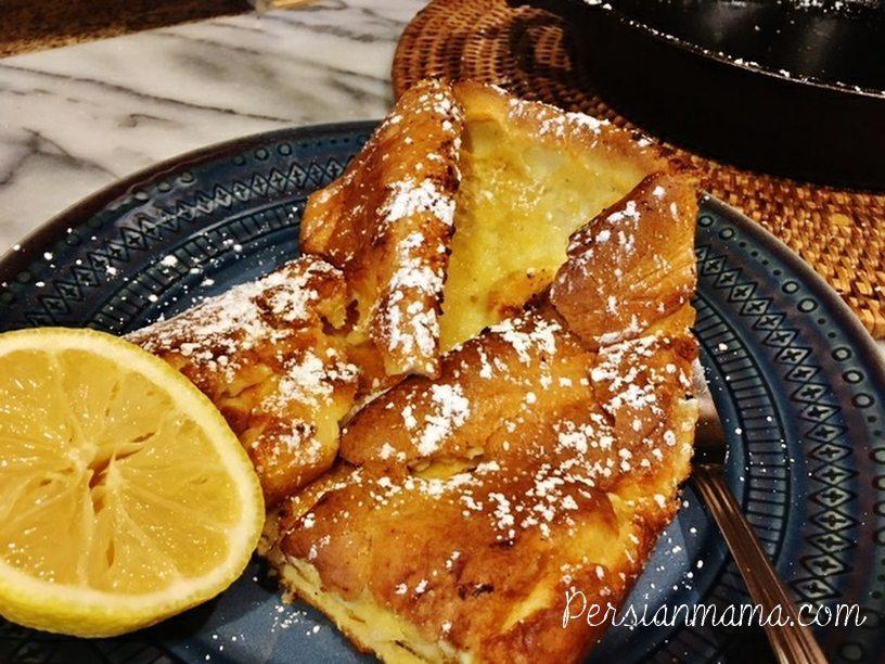Lemon half and German pancake 'Dutch baby' folded and cut in half